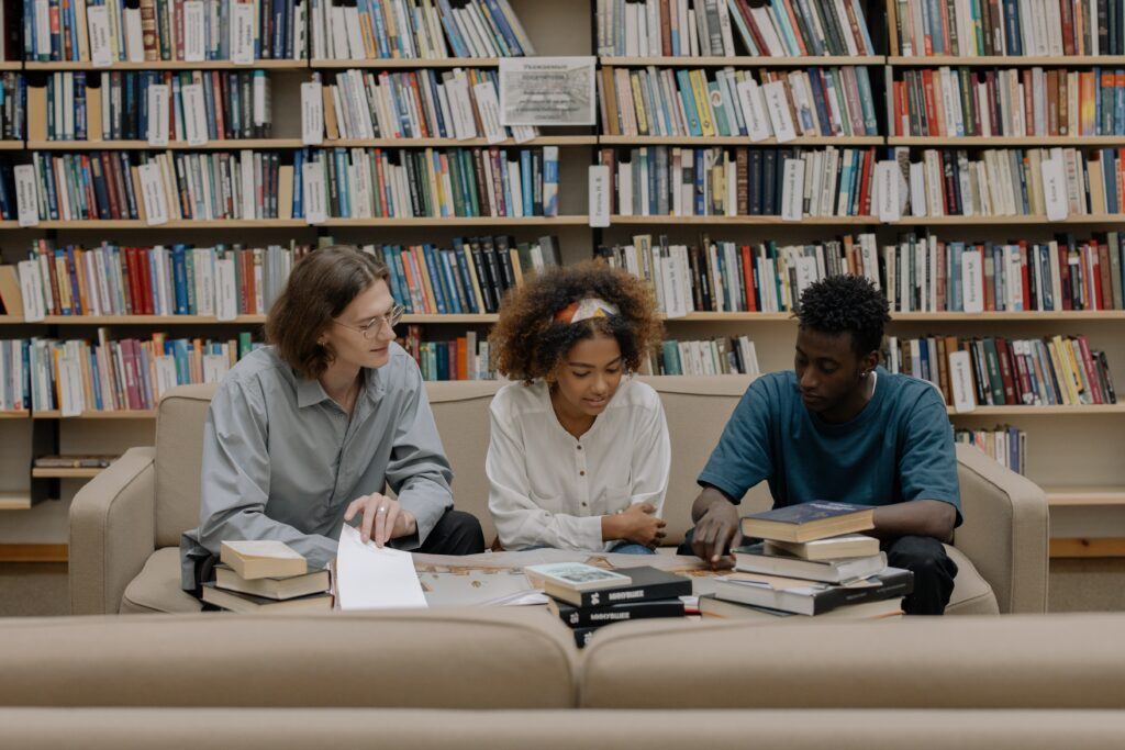 Three students studying together in a library filled with books.